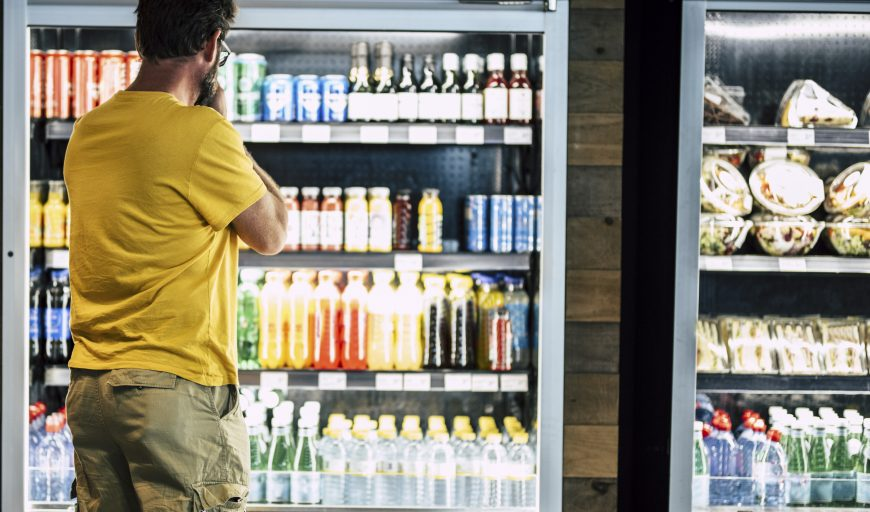 man alone and isolated at the supermarket or minimarket choosing his drink or snack in big fridge with lots of products - difficult select and choose