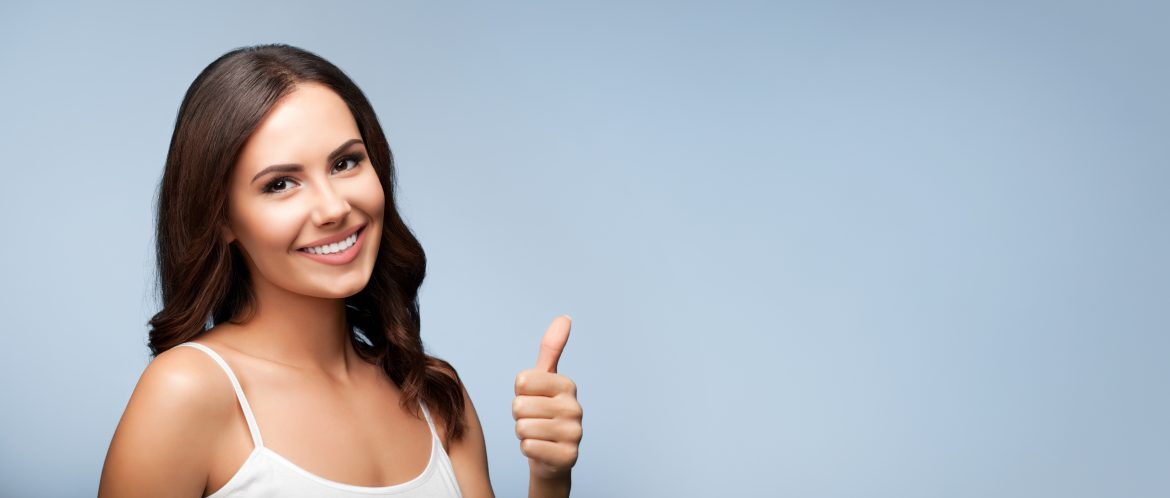 Portrait of beautiful cheerful smiling young woman showing thumb up gesture, on grey background, with blank copyspace area for text or slogan